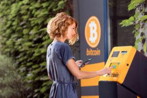 woman using a bitcoin atm
